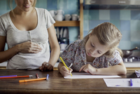 Pregnant mother looking on as daughter draws