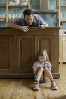 Father looking on as daughter plays video game