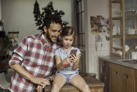 Father and daughter looking at smartphone together