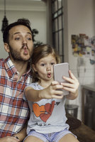 Father posing for selfie with daughter