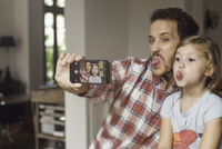 Father and daughter making funny faces selfie