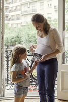 Mother preparing daughter for arrival of her new sibling