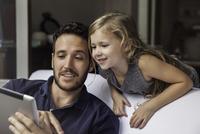Man showing daughter video streaming on digital tablet