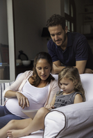 Father looking on as mother and daughter use digital tablet together