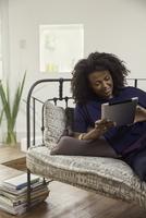 Woman streaming online video content on digital tablet