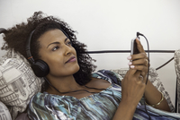 Woman relaxing to tunes playing on smartphone