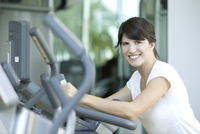 Woman working out in health club, smiling cheerfully