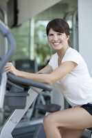 Woman exercising in health club, smiling cheerfully