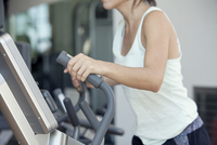 Woman using exercise machine in fitness club, cropped