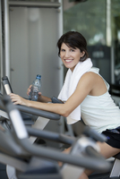 Woman exercising in fitness club with water bottle in hand