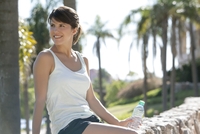 Woman relaxing in park with bottle of water