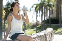 Woman drinking bottled water in park