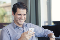 Man using smartphone and smiling cheerfully