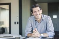 Businessman sitting at desk, smiling, portrait
