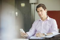 Businessman using smartphone at desk, portrait