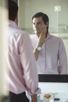 Man scrutinizing himself in mirror