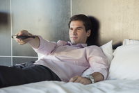 Man lying on bed, watching TV