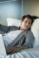 Man relaxing in bed with laptop computer