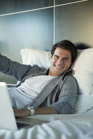 Man lying on bed, smiling cheerfully, portrait