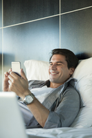Man relaxing in bed with multimedia smartphone