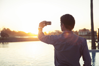 Man photographing sunset with smartphone
