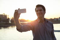 Man using smartphone to photograph himself in front of sunset