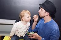 Father spoon feeding toddler