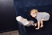 Toddler playing with infant sibling