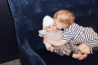 Toddler embracing infant sibling