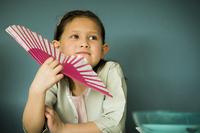 Little girl holding fan, portrait