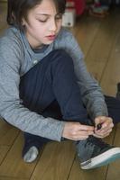 Boy tying his shoe