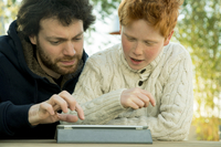 Father and son looking at digital tablet together