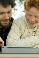 Father and son using digital tablet together