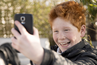 Boy using smartphone to take a selfie