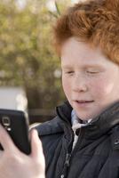 Boy using smartphone outdoors