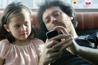Father and young daughter looking at smartphone together