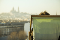 Person sitting in deckchair, looking at view of city