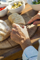 Man's hands cutting fresh loaf of bread outdoors