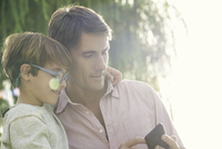 Father and son looking at smartphone outdoors, overexposure
