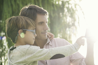 Father and son embracing outdoors, overexposure