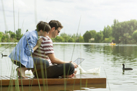 Couple using laptop computer on dock