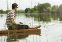 Man sitting on dock using laptop computer