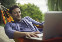 Man relaxing in hammock, using laptop computer