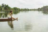Girl sitting on dock with feet dangling in lake, portrait 11001062677| 写真素材・ストックフォト・画像・イラスト素材|アマナイメージズ