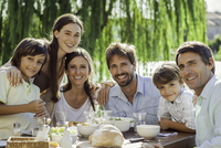 Family enjoying breakfast together outdoors, group portrait