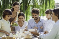 Family enjoying breakfast together outdoors 11001062713| 写真素材・ストックフォト・画像・イラスト素材|アマナイメージズ