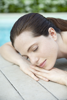 Young woman lying down, sunbathing with eyes closed, cropped