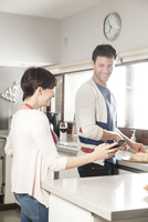 Couple looking at smartphone together while preparing food in kitchen