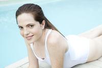 Woman sunbathing by pool, portrait