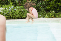 Girl doing cannonball into swimming pool